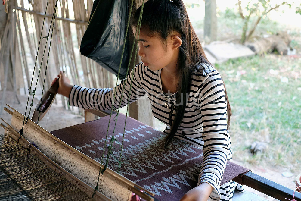 Handweaving organic cotton with a mutmee/tie dye design in the Phu Tai ethnic minority village of Ban Lahanam, Savannakhet province, Lao PDR. In Savannakhet most textiles are dyed with natural dyes according to longstanding traditions. 'Mutmee' is a tie-dye weaving technique that is special to the Phu-Tai ethnic group where the string is tied in each row wherever the colour is not wanted and then removed after dyeing. Although only plainweave, the weaving is slow as each weft row needs to be lined up to maintain the pattern.