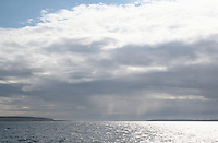 Sunlight and storm clouds over the Aran Islands in Galway Ireland