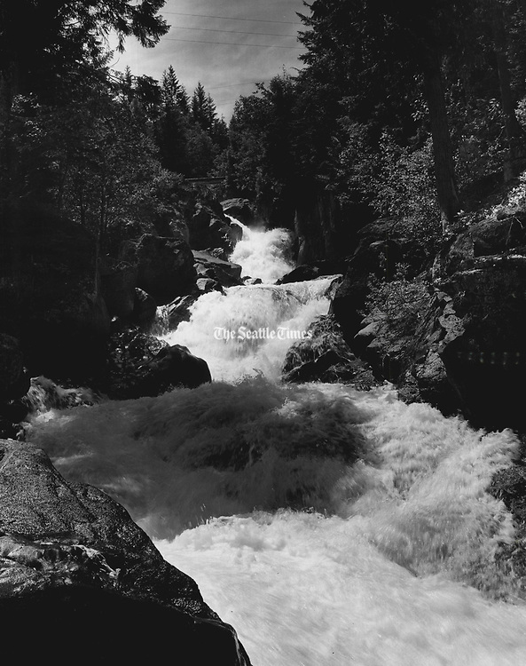 A Few miles west of the little town of Scenic, the Stevens Pass Highway crosses Deception Creek, one of hundreds of streams that tumble spectacularly down the west slope of the Cascades. (Josef Scaylea / The Seattle Times, 1960)