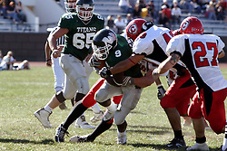 07 October 2006: Marcus Dunlop is stopped by a trio of Red Man defenders. The Titans of Illinois Wesleyan University started off strong with a touchdown on the 2nd play from scrimmage in the game.  The Titans led most of the way, but failed to maintain the lead in the 4th quarter giving up the decision of this CCIW conference game to the Red Men of Carthage by a score of 31 - 28. Action was at Wilder Field on the campus of Illinois Wesleyan University in Bloomington Illinois.<br />
