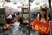 """Pachinko parlors in Japan are packed and popular with the older set. Osaka, Japan. (The girl holds a sign that says: """"right now all of the machines have 'no panku',"""" which means they have turned off the part of the machine that randomly stops you from getting balls when you've started getting them. (The point of the game is to collect more and more balls, but sometimes when you get a ball somewhere, that makes them start streaming out, there is a function of the machine which will stop them after some random amount, so you usually get fewer; they've turned that function off). (Supporting image from the project Hungry Planet: What the World Eats.)"""