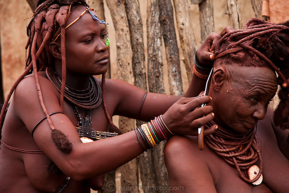 Viahondjera Musutua, a Himba woman, uses a penknife to fix the hair of another Himba woman in the small village of Ondjete in northwestern Namibia. (Viahondjera Musutua is featured in the book What I Eat: Around the World in 80 Diets.)