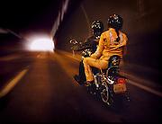 A couple rides their motorcyle through a tunnel