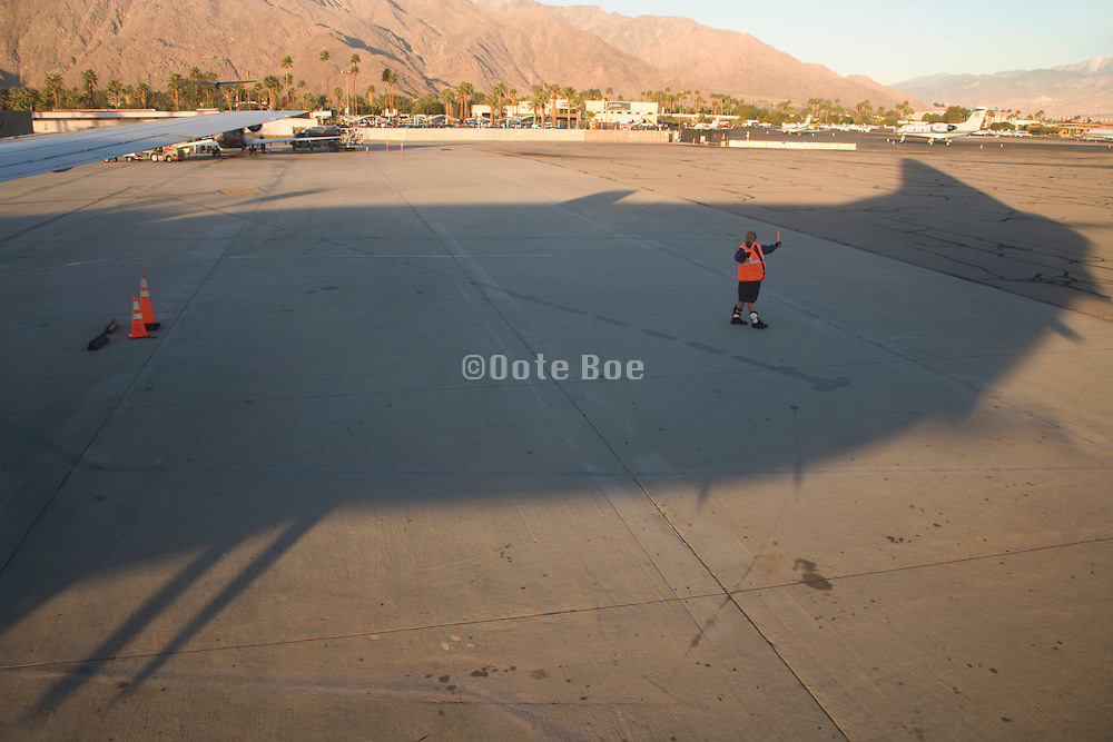 ground crewman directing an aircraft before takeoff airport Palm Springs