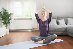 Young woman doing lotus pose yoga on exercise mat in living room, Bavaria, Germany