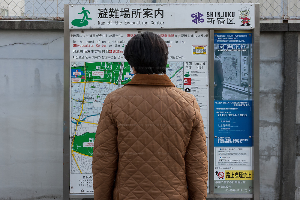 A Japanese man checks the evacuation map after a magnitude .9 earthquake hit the Tohoku region of north east Japan causing tremors in Tokyo that stopped the train and cellphone networks. Many people were stranded in the centre of Tokyo over night. Tokyo, Japan Friday March 11th 2011