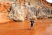 10 year old child doing a cartwheel in the red mud of the Fairy Stream (Suoi Tien), Mui Ne, Vietnam