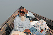Bangladesh, Jamuna River, (called the Brahmaputra River in India) near the town of Gaibanda. This is the  boat based Friendship non-profit organization (NGO), who provide health care and vocational traing  for locals. This local man has recently had a cataract operation on his eyes and is wearing dark sunglasses.
