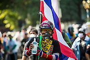 26 DECEMBER 2013 - BANGKOK, THAILAND: An anti-government protestor marches towards a riot against Thai police in Bangkok. Thousands of anti-government protestors flooded into the area around the Thai Japan Stadium to try to prevent the drawing of ballot list numbers by the Election Commission, which determines the order in which candidates appear on the ballot of the Feb. 2 election. They were unable to break into the stadium and ballot list draw went as scheduled. The protestors then started throwing rocks and small explosives at police who responded with tear gas and rubber bullets. At least 20 people were hospitalized in the melee and one policeman was reportedly shot by anti-government protestors.      PHOTO BY JACK KURTZ