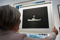 "© Licensed to London News Pictures. 03/05/2017. London, UK. A buyer shows her purchase of ""Ghost Ship"" by Dorothy Cross at the preview of the 32nd London Original Print Fair at the Royal Academy of Arts in Piccadilly.  51 international specialist dealers are presenting works in the print medium to buyers from 4 May to 7 May. Photo credit : Stephen Chung/LNP"