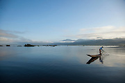 A fisherman uses a conical net, a traditional method, to catch fish on Inle Lake, Myanmar