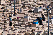 Jews at prayer over a grave at the Ancient Jewish Cemetery on Mount of Olives, Jerusalem