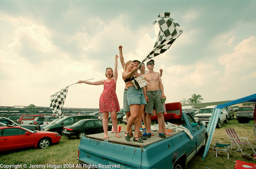 A group of friends gather in the infield to cheer for their favorite driver during the Indy 500.