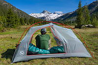 Adult male backpacker relaxing in backcountry camp in Upper Lostine River Valley Eagle Cap Wilderness Oregon