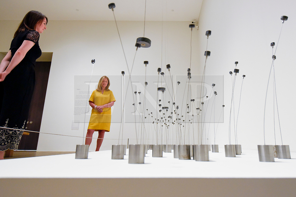 """© Licensed to London News Pictures. 02/07/2019. LONDON, UK.  Staff members view """"Magnetic Fields"""", 1969, by Takis. Preview of a new display by the Greek sculptor Takis at Tate Modern.  The retrospective features over 80 works in Takis' largest exhibition in the UK to date and combines works involving magnetism, light and sound.  The show runs 3 July to 27 October.  Photo credit: Stephen Chung/LNP"""