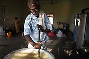 Vadivelu, 75, stirs the rice in the kitchen at the Tamaraikulum Elders village, Tamil Nadu, India