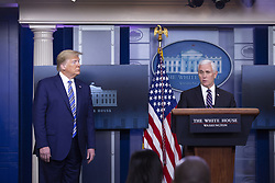 United States President Donald J. Trump, left, listens as United States Vice President Mike Pence delivers remarks on the Coronavirus pandemic during a news conference in the James S. Brady Press Briefing room at the White House in Washington D.C., U.S., on Sunday April 19, 2020. Speaker of the United States House of Representatives Nancy Pelosi (Democrat of California) stated that lawmakers are close to a deal with United States Secretary of the Treasury Steven T. Mnuchin regarding a second round of small business loans for businesses impacted by Coronavirus. Credit: Stefani Reynolds / CNP