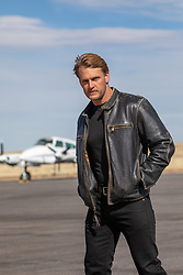sexy blond man in a leather jacket by a private jet