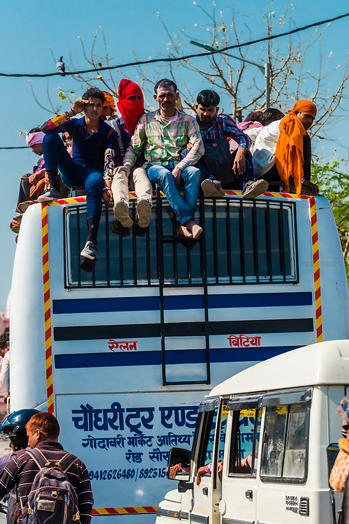 People riding on the roof of a bus departing the Huranga Holi festival in Baldeo, Uttar Pradesh, India.