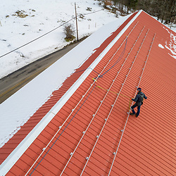 A PV Squared employee installing the rails for a solar panel installation on a barn in Leyden, Massachusetts.