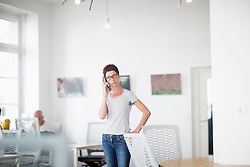 Mature woman talking on mobile phone in the office, Freiburg im Breisgau, Baden-W¸rttemberg, Germany