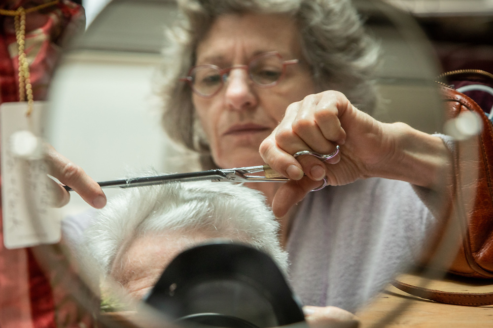 """""""I'm not comfortable with sitting in a barber chair and haven't had a professional haircut in nine months.  I am amazed how much confidence Mitzi has gained this past year.  This is one of the best haricuts I have ever had.""""  -Mitzi Mishler gives her husband, Clark, a covid hair cut at their home in Calistoga."""