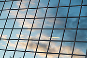 Clouds in the sky reflected in the square glass panels of the Northern & Shell Building in London, England, United Kingdom.