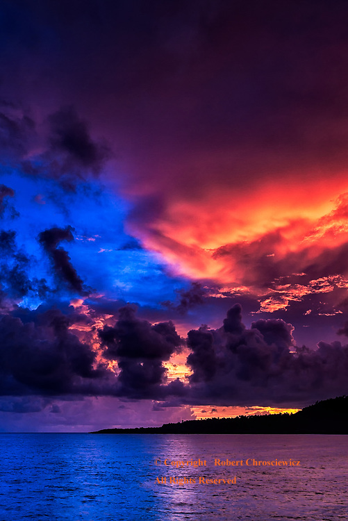 The Red and Blue of Dawn: The vivid red and blue of dawn fills the sky and is reflected in the topical ocean waves in Baracoa Cuba.