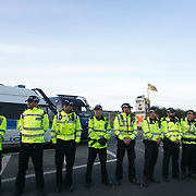 13 local activists locked themselves in specially made arm tubes to block the entrance to Quadrilla's drill site in New Preston Road, July 03 2017, Lancashire, United Kingdom. Police line protecting the Quadrilla fracking site.The 13 activists included 3 councillors; Julie Brickles, Miranda Cox and Gina Dowding and Nick Danby, Martin Porter, Jeanette Porter,  Michelle Martin, Louise Robinson,<br /> Alana McCullough, Nick Sheldrick, Cath Robinson, Barbara Cookson, Dan Huxley-Blyth. The blockade is a repsonse to the emmidiate drilling for shale gas, fracking, by the fracking company Quadrilla. Lancashire voted against permitting fracking but was over ruled by the conservative central Government. All the activists have been active in the struggle against fracking for years but this is their first direct action of peacefull protesting. Fracking is a highly contested way of extracting gas, it is risky to extract and damaging to the environment and is banned in parts of Europe . Lancashire has in the past experienced earth quakes blamed on fracking.