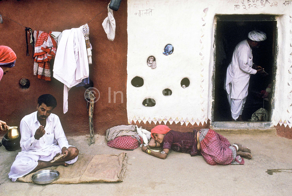 "Bhiya Ram lunching on Millet chapati nd milk, as his sistare looks on lazily, The ""Bishnoi"" farmers caste in the village of Guda Vishnoyan, Rajasthan, India"