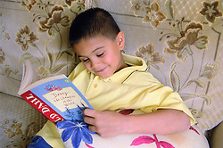 Young boy sitting on sofa reading story book,