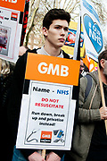 Tens of thousands of health workers, activists and members of the public protested against austerity and cuts in the NHS National Health Service on March 4th 2017 in London, United Kingdom. A young man holds a GMB General trade Union placard based on a patients card with the instruction NHS do not resuscitate.