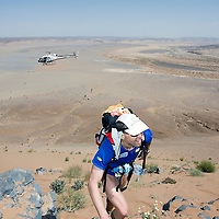 26 March 2007:  A runner reaches summit of jebel El Otfal, 947 meters and an average 25% slope, as an helicopter is passing by, during the second stage (21.7 miles) of the 22nd Marathon des Sables between Khermou and jebel El Otfal. The Marathon des Sables is a 6 days and 151 miles endurance race with food self sufficiency across the Sahara Desert in Morocco. Each participant must carry his, or her, own backpack containing food, sleeping gear and other material.
