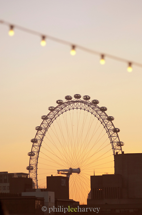 The London Eye, a large Observation Wheel, silhouetted by a low sun amongst buildings in London, UK