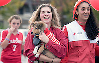 """Sophomore Hannah Mansfield carries her dog Charlie dressed in theme for the American Red Cross float during the Laconia High School Homecoming Parade.  This year's parade was """"Colors for a Cause"""" including United Nations Environment Programme (Seniors), American Cancer Society (Juniors) and NH Humane Society (Freshmen).   (Karen Bobotas/for the Laconia Daily Sun)"""