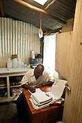 Nairobi, June 2010 -  The pharmacist at the  Agape Hope Center works  at his desk. He is part of a sophisticated program to dispense basic medicine as well as antiretrovirals in what, so far, is a successful effort to limit transmission of HIV to newborn babies.