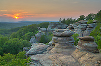 The sun sets behind two pillars at Garden of the Gods, Illinois. This part of the Shawnee Hills is filled with strange rock formations and extensive views of the surrounding forest.<br /> <br /> Date Taken: July 22, 2014