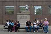 Visitors to the capital rest on the plinth under the Londion Bridge griffin, the southern-most boundary on the Southwark end of Londons historic financial district, on 14th August 2017, in Southwark, London, England.