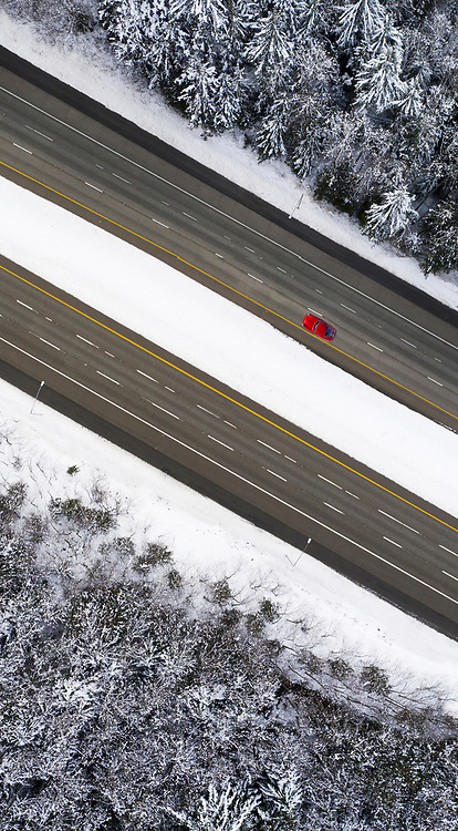 Image of a Red Porsche 356 driving through a winter landscape of Evergreen firs in the North Cascades, Washington, Pacific Northwest by Randy Wells