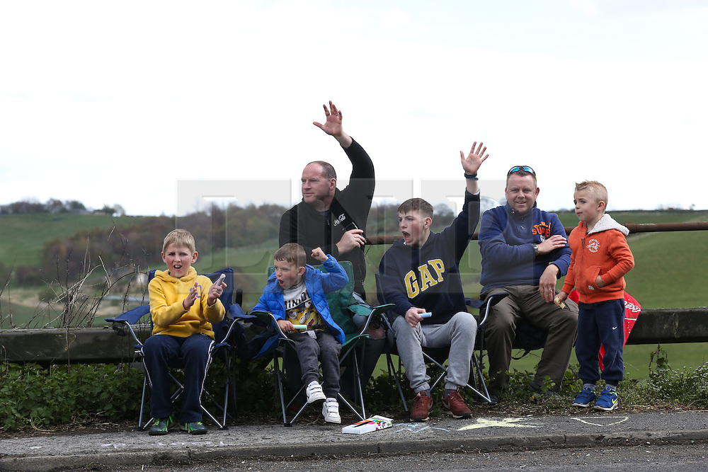 © Licensed to London News Pictures. 30/04/2016. Harewood, UK. Spectators wave to passing cars as they wait for the riders to ascend the climb in Harewood near Leeds in West Yorkshire during the second stage of the 2016 Tour De Yorkshire. The three-day road cycling race held annually across Yorkshire is in it's second year. Photo credit : Ian Hinchliffe/LNP