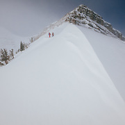 Natalie Segal and Andrew Whiteford hike on Cody Peak in the backcountry of the Teton Mountain Range, Wyoming.