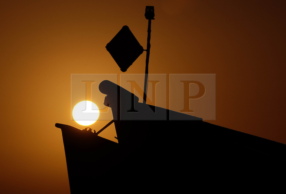© Licensed to London News Pictures. <br /> 03/05/2016. <br /> Saltburn by the Sea, UK. <br /> <br /> The sun rises between the bows of fishing boats at Saltburn by the Sea in North Yorkshire.<br /> <br /> Photo credit: Ian Forsyth/LNP