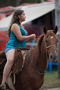Young Brazilian Gaucha cowgirl female, riding a horse. Gaucho cowboy Rodeo, Flores de Cunha, Rio Grande do Sul.