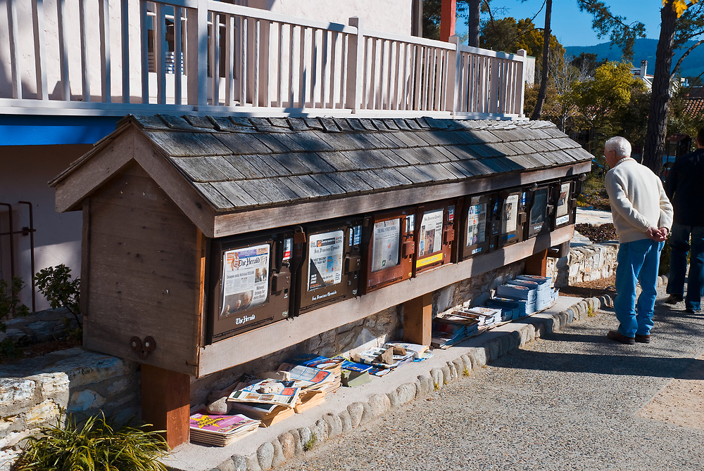 SUBJECT: News Boxes IMAGE: A gentleman peruses the evening headlines of newspapers esconced under a shingled row of boxes. - Only in California