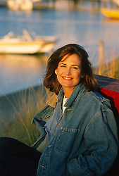 portrait of a woman sitting on the shore of the Sag Harbor boating area