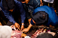 From the market in Bac Ha, in northern Vietnam. Men point to a section on a slab of pork for a game that tests a man's knife-wielding skills.