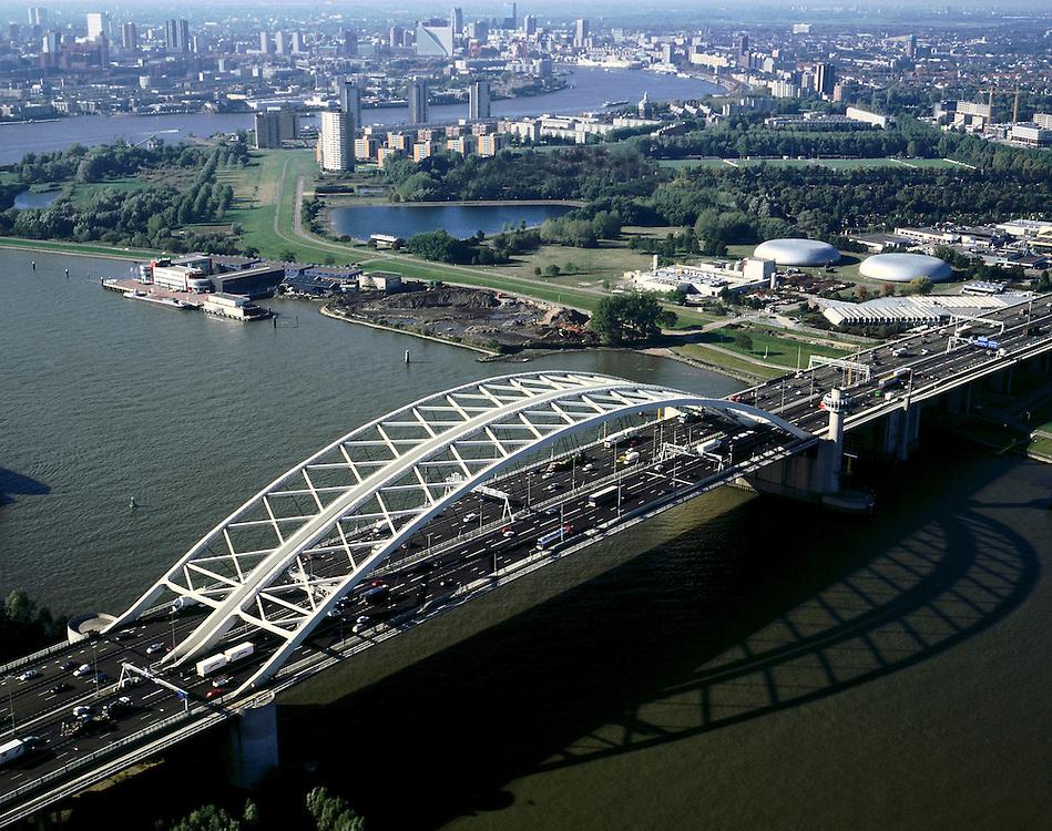 Nederland, Rotterdam, Nieuwe Maas, 08-03-2002; luchtfoto (25% toeslag); Van Brienenoordbrug (met rijksweg A16) over de rivier vormt een vd belangrijkste Noordzuid verbindingen; links boven de brug de drinkwaterleiding (met ronde bassins), aan de horizon de skyline van Rotterdam, met hoogbouw in het stadscentrum..Foto Siebe Swart