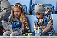 A little Girl (Coventry City) sits reading her match day programme during the EFL Sky Bet League 1 match between Coventry City and Bristol Rovers at the Ricoh Arena, Coventry, England on 7 April 2019.