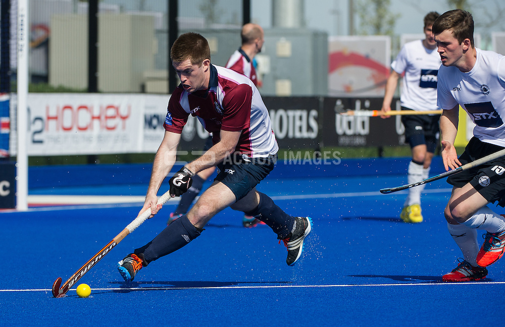 Wimbledon's Henry Weir is watched by Simon Faulkner of East Grinstead. East Grinstead v Wimbledon -  Now: Pensions Men's Hockey League Championship Final, Lee Valley Hockey & Tennis Centre, London, UK on 12 April 2015. Photo: Simon Parker