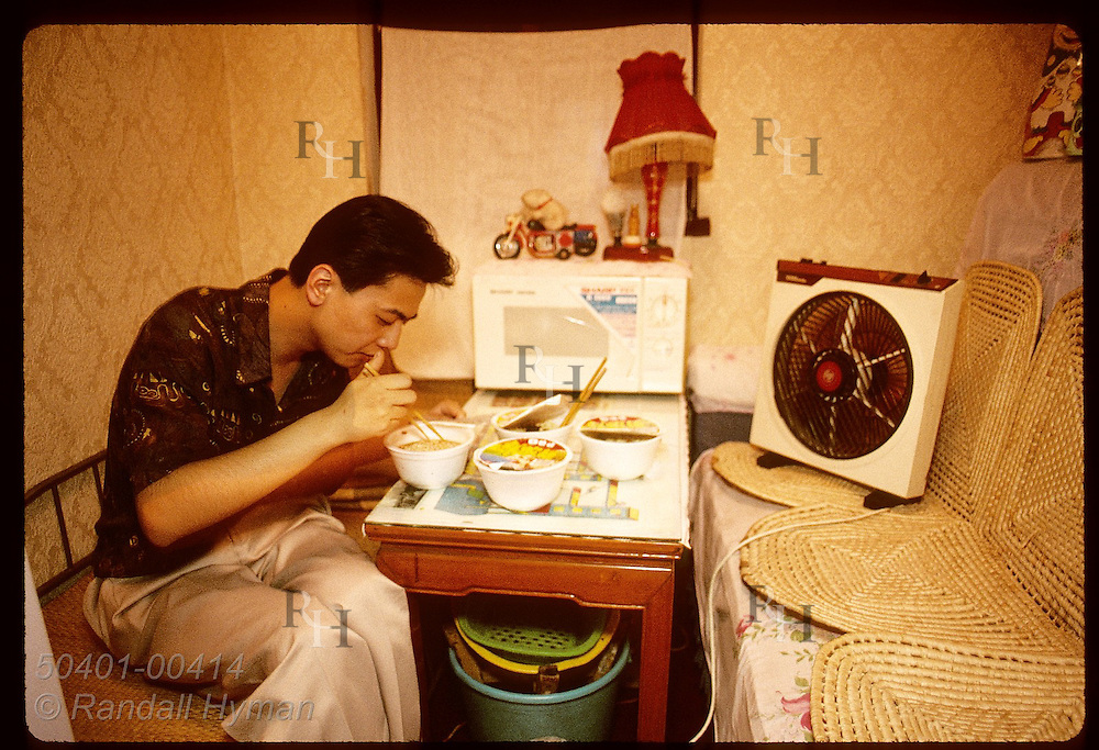 Businessman eats dinner of noodle soup in small apartment after long day at office in Shanghai. China
